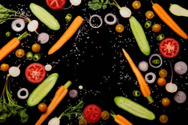 top view of fresh scattered vegetable slices with salt isolated on black