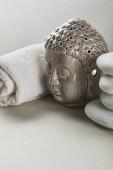 pamut törölköző, kövek, Buddha szobor fehér asztalon izolált szürke