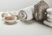 sea salt and clay powder in bowls, cotton towel, stones, bath bomb and Buddha figurine on white table isolated on grey