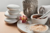 clay and sea salt in bowl near Buddha figurine and spa stones on marble circle isolated on grey