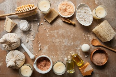 top view of natural cosmetics and beauty supplies near decorative candles on textured weathered beige surface