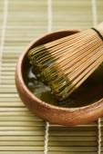 selektivní zaměření zeleného prášku na matča a bambusový metan v dřevěné misce na stolní rohoži