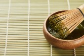 green matcha powder and bamboo whisk in wooden bowl on table mat with copy space