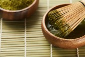 selective focus of green matcha powder and bamboo whisk in wooden bowl with tea