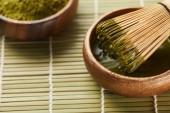 selektivní zaměření zeleného prášku na Matcha a bambusového metlu v dřevěné misce s čajem
