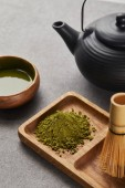selective focus of green matcha powder and bamboo whisk on wooden board near black teapot and bowl with tea