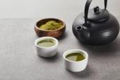 selektivní zaměření zeleného prášku na Matcha v dřevěné misce blízko černého čajového hrnce a bílých šálků s čajem z šedého kamene