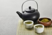 selective focus of green matcha powder in wooden bowl near black teapot and cups with tea on bamboo table mat
