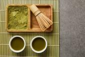 pohled na zelený matča prášek s bambusovou metou na dřevěné desce blízko bílých pohárků se zeleným čajem na stolní rohoži