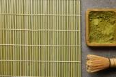 pohled na zelený matča prášek na dřevěné desce v blízkosti bambusových metan a stolní rohože