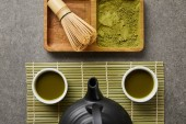 top view of white cups with tea and black teapot on green table mat near bamboo whisk and matcha powder on board
