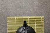 Fotografie pohled na zelenou bambusovou podložku s černým čajovým hrnku na šedé ploše