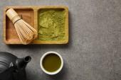 pohled na bambusovou metlu a prášek Matcha na palubě blízko černé čajové konvice a bílého šálku se zeleným čajem