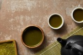 top view of matcha powder, bowl and cups with green tea on aged surface near bamboo table mat and black teapot