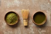 Nejlepší pohled na matča čaj a prášek v dřevěné misce s bambusovou metou na staré hladině