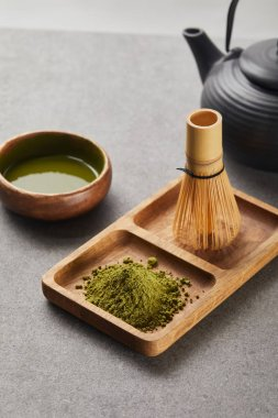 Selective focus of green matcha powder and bamboo whisk on wooden board near black teapot and bowl with tea stock vector