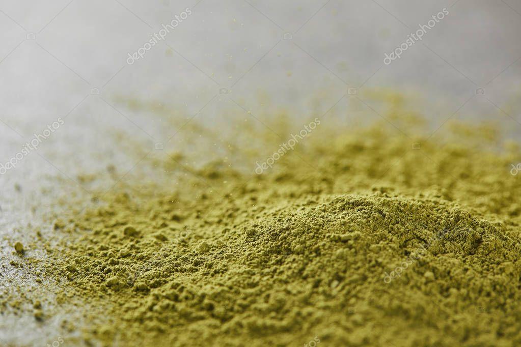 selective focus of green matcha powder on table