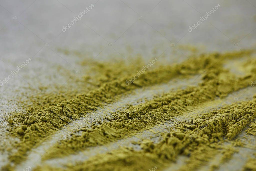 selective focus of green matcha powder on grey table