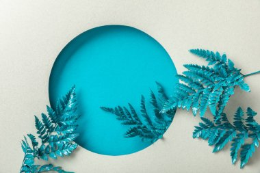 blue fern leaves in round hole on white paper