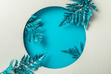 blue decorative fern leaves in round hole on white paper
