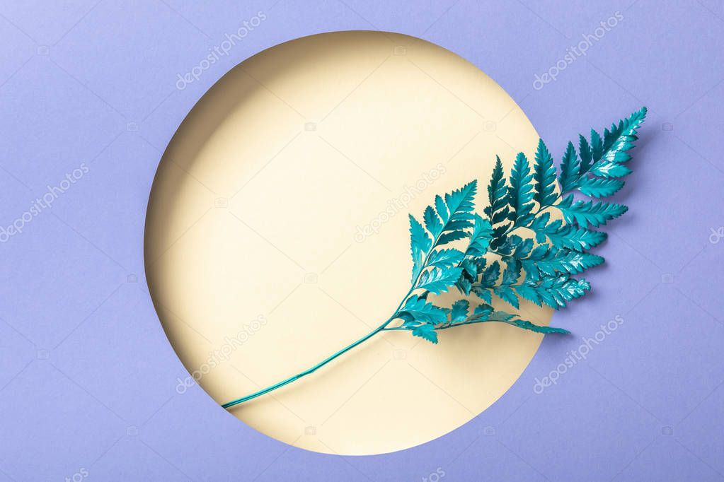 Blue fern leaf in round beige hole on purple paper stock vector