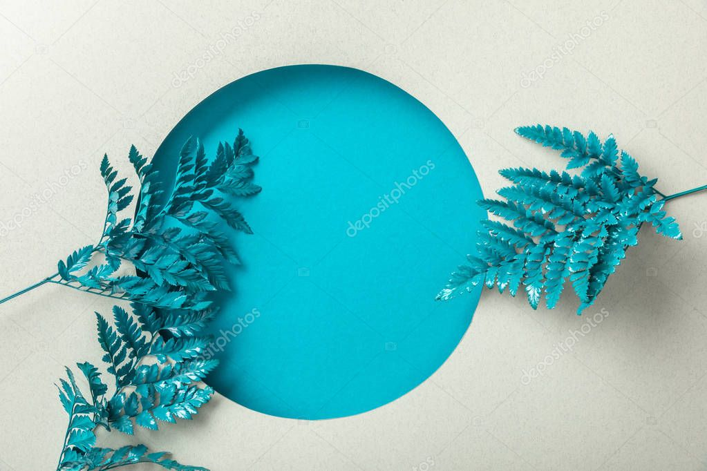 Blue decorative fern leaves near round hole on white paper stock vector