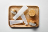 pohled na malé prázdné skleničky a smetanové trubky na dřevěném tácku na bílém