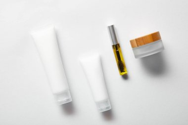 Top view of cream tubes with hand cream, empty jar and mascara bottle with oil on white stock vector