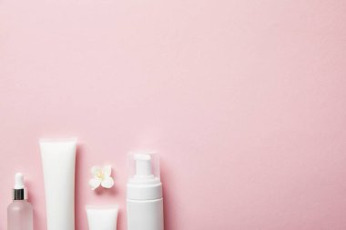 top view of empty cosmetic glass bottle, cream tubes with cream, cosmetic dispenser and jasmine flower on pink