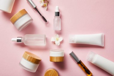 top view of jars, cream tubes with hand cream, cosmetic glass bottles, mascara bottles and jasmine flower in middle on pink