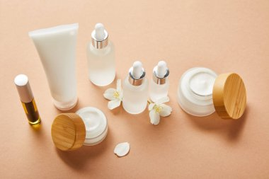 mascara bottle with natural oil, cream tube, cosmetic glass bottles, open jars with cream and jasmine flowers on beige