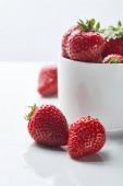 lahodné červené sladké jahody v šálku na bílém pozadí