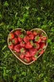 pohled na ekologické jahody ve tvaru dřevěné srdeční desky na zelené trávě