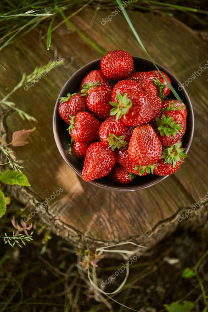 top view of red strawberries in bowl on stump