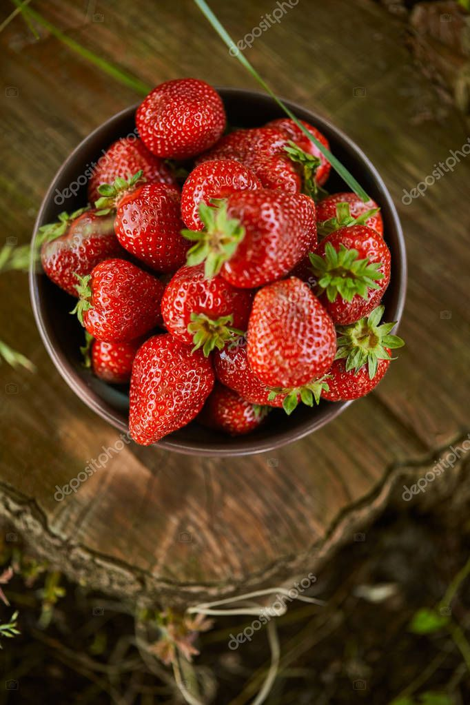 top view of red fresh strawberries in bowl on stump