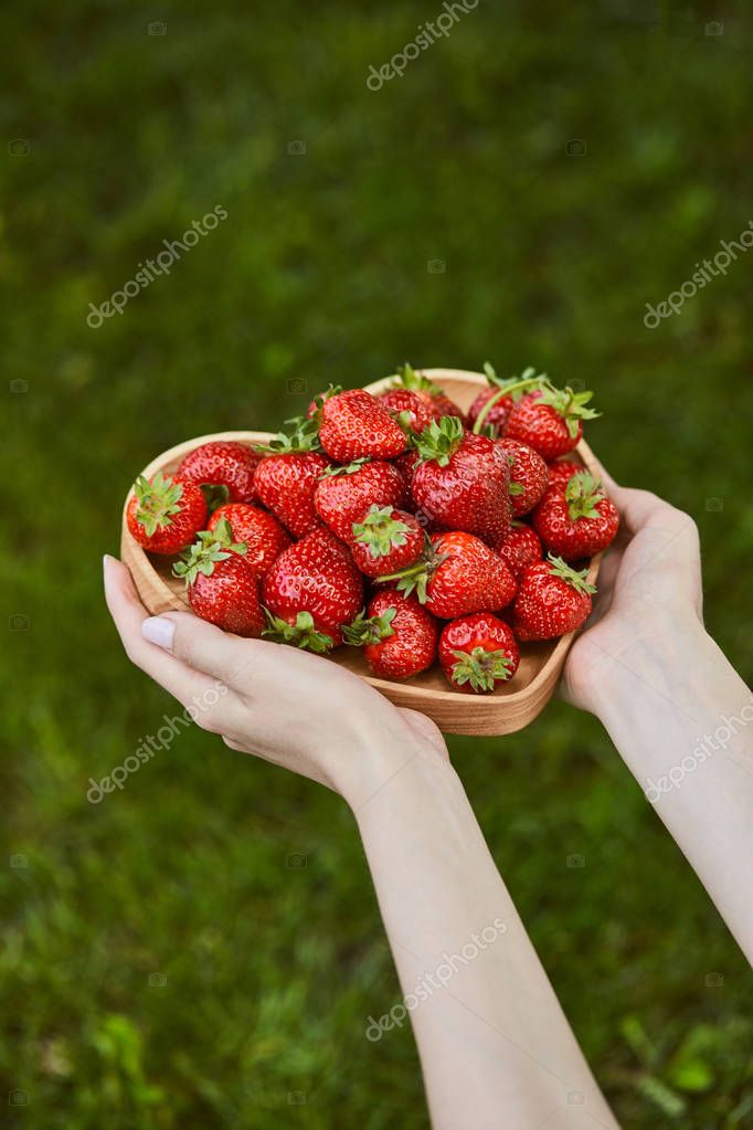cropped view of woman holding heart shaped plate with sweet strawberries