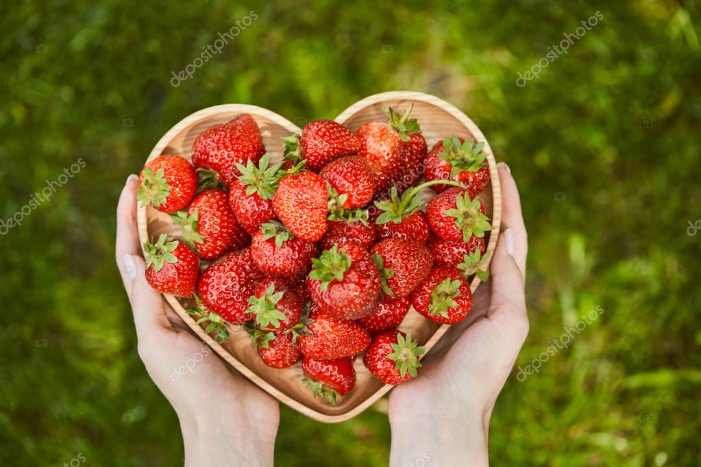 cropped view of woman holding heart shaped plate with organic strawberries