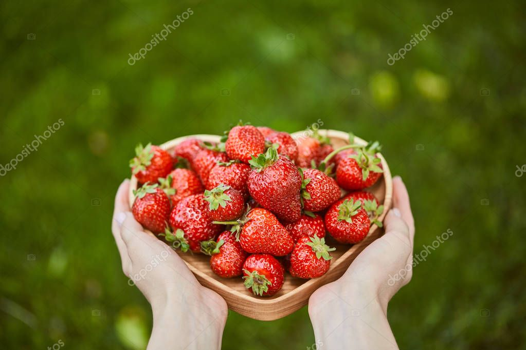 cropped view of woman holding heart shaped plate with raw strawberries