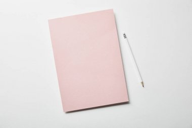 top view of pink paper and pencil on white surface