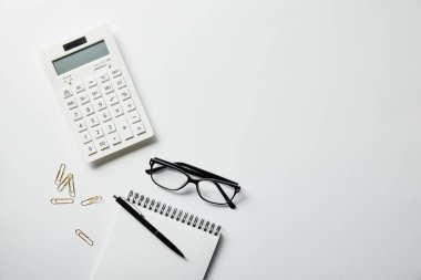top view of stationery, calculator and notebook with pen on white surface