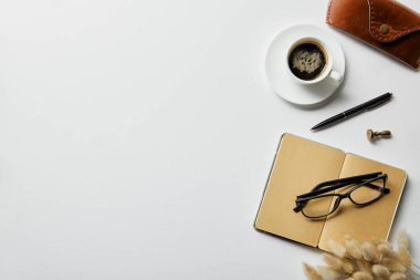 top view of coffee, notepad with pen and case on white surface