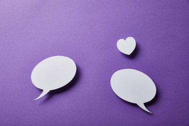 white speech bubbles and small paper heart on purple surface