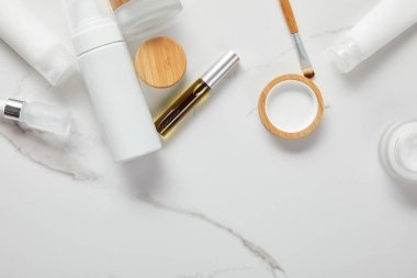 cropped view of cream tubes, cosmetics jars, dispenser and glass bottle with eye brush on white surface