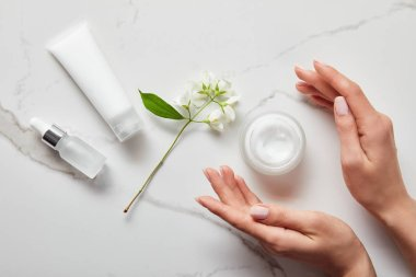 top view of woman hands near cosmetic glass bottle, jar with cream, moisturizer tube and jasmine on white surface