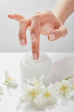 Cropped view of woman hand touching cream in jar near jasmine flowers on white surface stock vector
