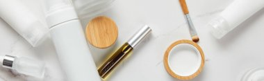 panoramic shot of cream tubes, cosmetics jars, dispenser, glass and mascara bottles with eye brush on white surface
