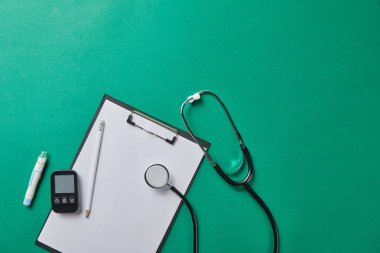 top view of blood lancet and stethoscope near glucometer and pencil on folder on green background