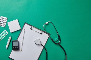 top view of blood lancet, sticky notes, blister packs and stethoscope near glucometer and pencil on folder on green background