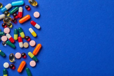 various colorful medical pills on blue surface