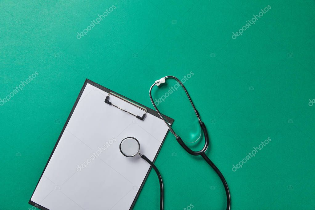 Top view of stethoscope near folder with blank paper isolated on green stock vector